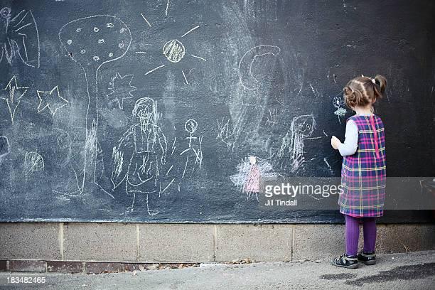 young girl drawing on blackboard