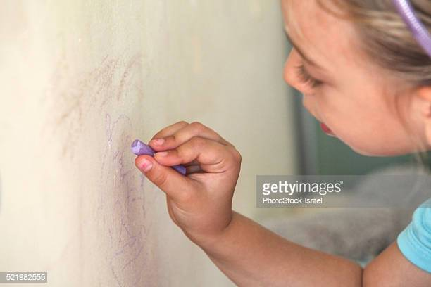 Young girl drawing on wall with chalk