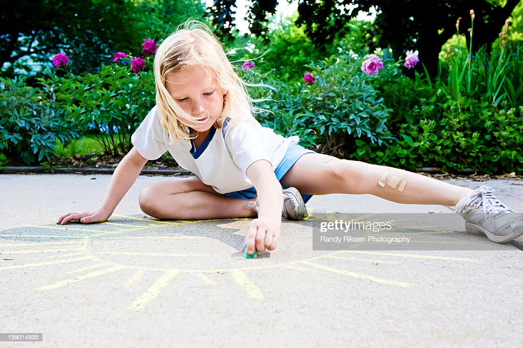 Young girl drawing sunshine with sidewalk chalk : Stock Photo