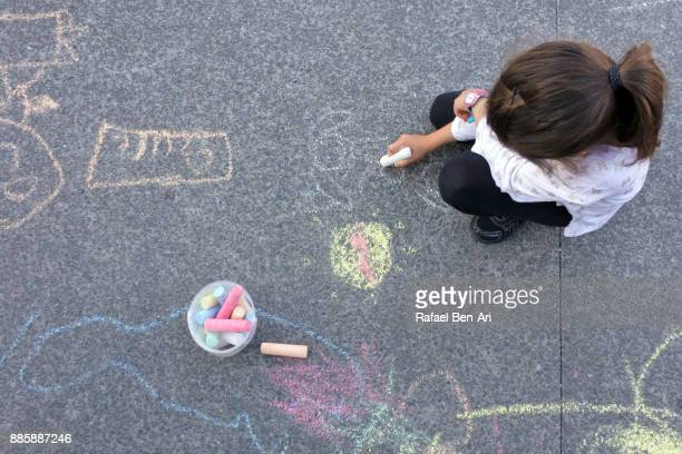 Young girl drawing with chalks on sidewalk