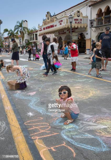 A young girl draws chalk pictures on State Street in advance of the annual Summer Solstice Parade an event that has evolved into equal parts of Mardi...