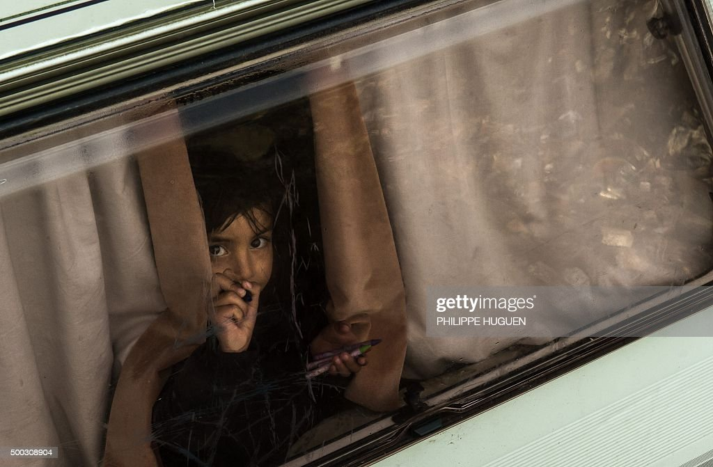 A young girl draws with a crayon on the window of a trailer at the migrant camp known as the 'Jungle' in Calais on December 7, 2015. / AFP / PHILIPPE