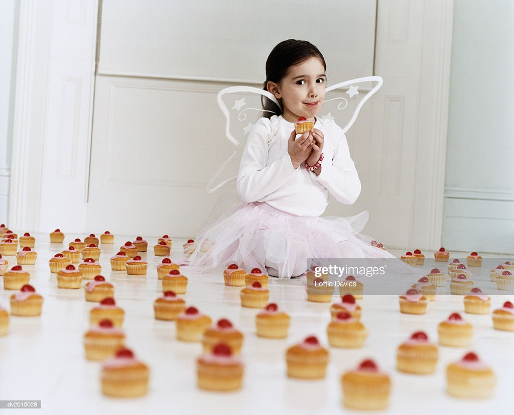 Young Girl Dressed as a Fairy Sitting Amongst a Large Selection of Cup Cakes Licking Her Lips and Holding a Cupcake : Stock Photo
