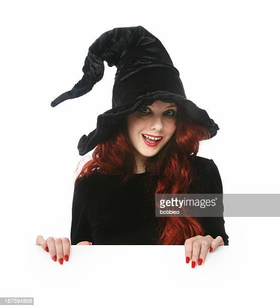 Young girl dressed as a witch isolated on white