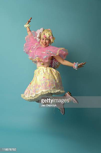 Young girl dressed as doll, jumping