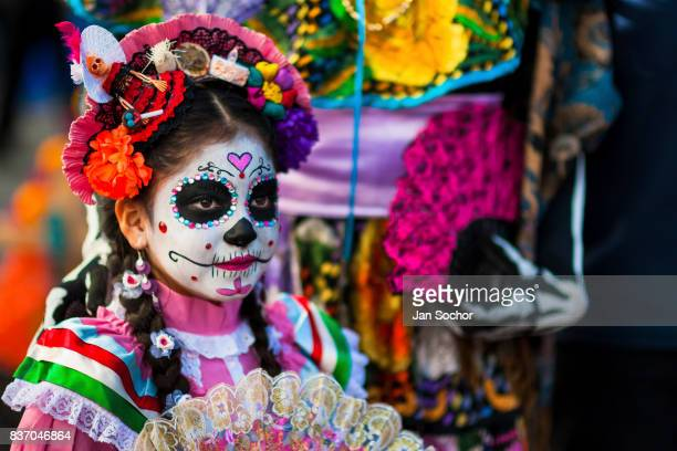 A young girl dressed as La Catrina a Mexican pop culture icon that represents Death looks on during the Day of the Dead festivities on October 28...