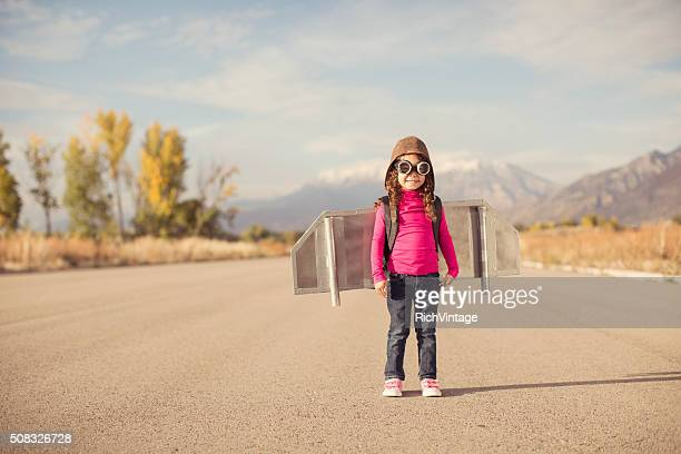 Young girl dressed as pilot wearing jet pack