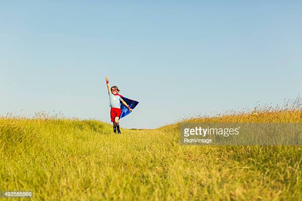 Young Girl dressed as Superhero Running in Grass