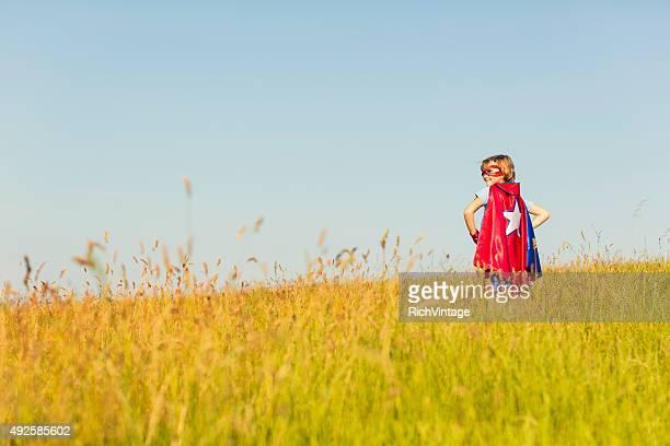Jeune fille habillée comme des super-héros en herbe debout