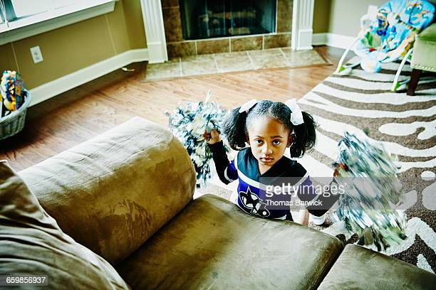 young girl dressed for cheerleading in living room - black cheerleaders stock photos and pictures