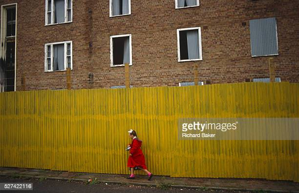 Young girl dressed in a red coat and pink socks walks half-way along a bright yellow stretch of corrugated sheet metal that screens off a derelict...