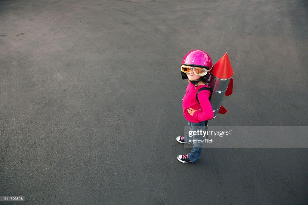 Junge gekleidet in einen roten rocket Anzug auf Asphalt : Stock-Foto