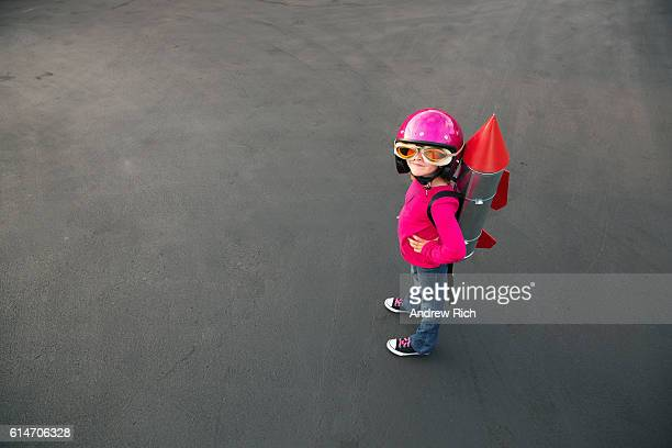 Young girl dressed in a red rocket suit on blacktop