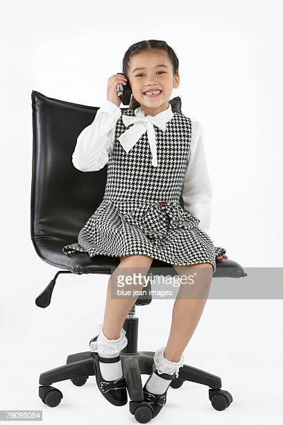 A young girl dressed in business attire making a call on her cell phone.