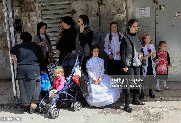 A young girl dressed in costume sits amongst a group of women during the feast of Purim in the ultraOrthodox Jews neighbourhood of Mae Sharim...