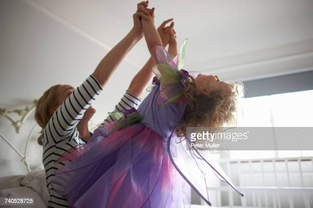 Young girl dressed in fairy costume, holding hands with mother, leaning back
