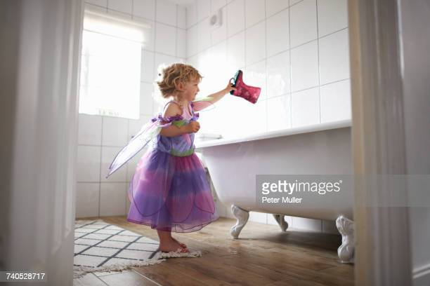 Young girl dressed in fairy costume, holding rubber boot over bathtub