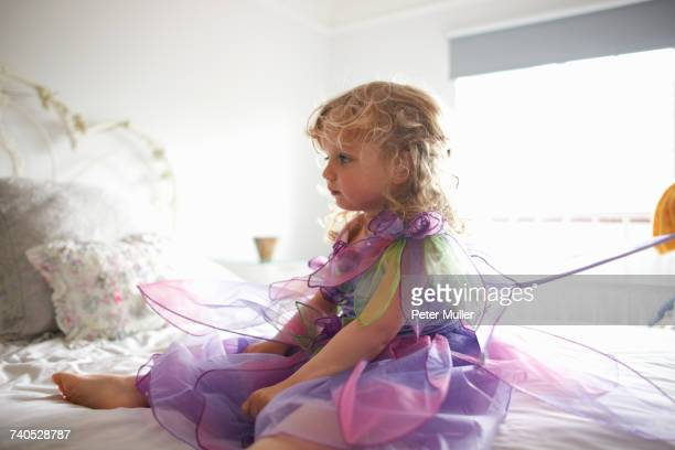 Young girl dressed in fairy costume, sitting on bed