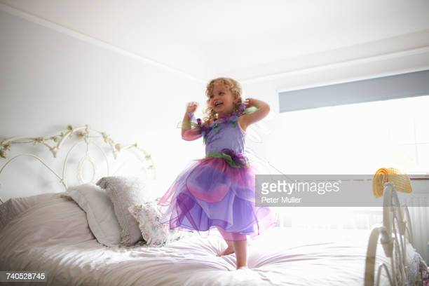 Young girl dressed in fairy costume, standing on bed, smiling
