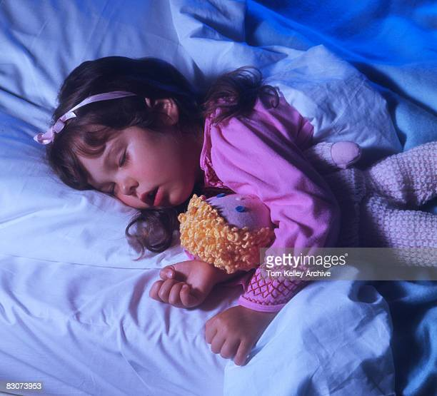 A young girl dressed in pink pajamas and ribbon in her hair sleeps in a bed with a doll clutched under one arm California 1950s