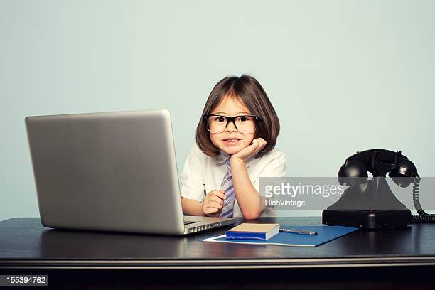 Young Girl Dressed in Tie at Laptop in Office