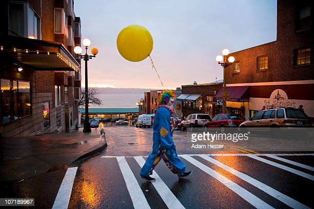 a young girl dressed up as a clown walking. - clown stock-fotos und bilder