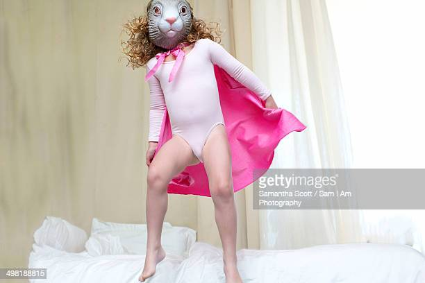 young girl dressed up as a rabbit princess dancing on bed - leotard stock photos and pictures