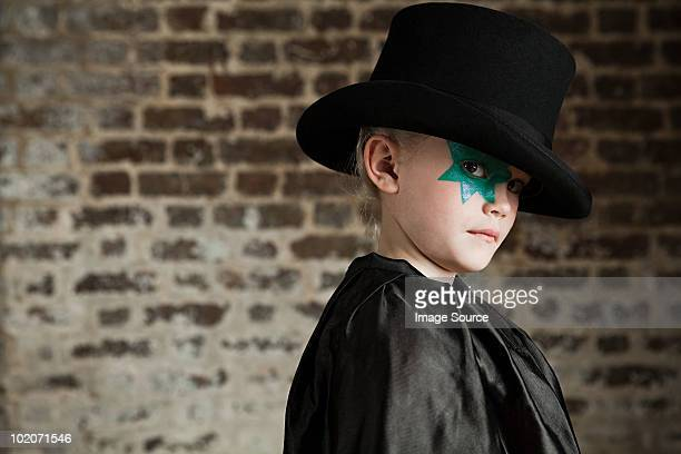 Young girl dressed up as magician wearing top hat
