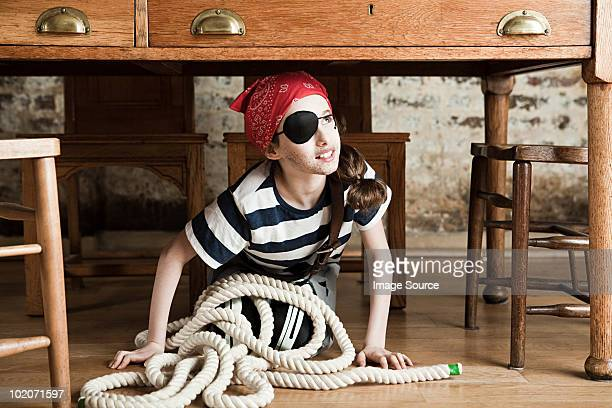 young girl dressed up as pirate, under desk - female pirate stock photos and pictures