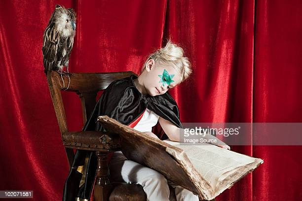 Young girl dressed up as wizard asleep with spell book