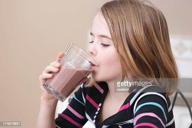 Young girl drinking a glass of chocolate milk