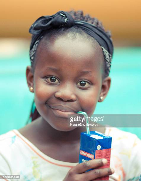 young girl drinking a juice box - juice carton stock photos and pictures