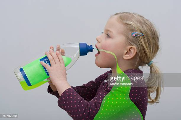 A young girl drinking from a bottle of cleaning fluid