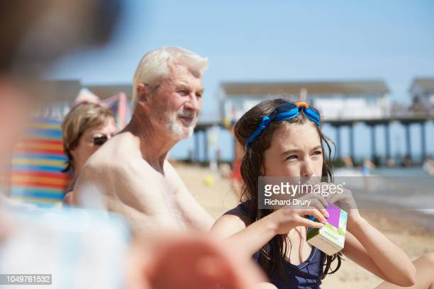 young girl drinking from juice from a carton at the beach - carton stock photos and pictures