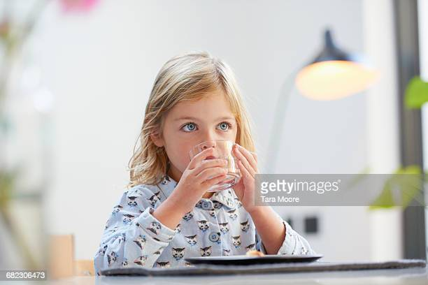 young girl drinking glass of water at breakfast