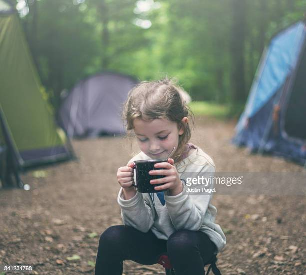 Young Girl drinking hot drink whilst camping