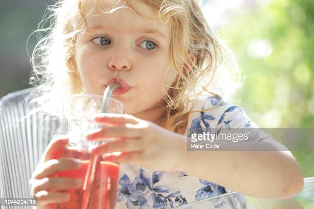 Young girl drinking juice through a reusable straw