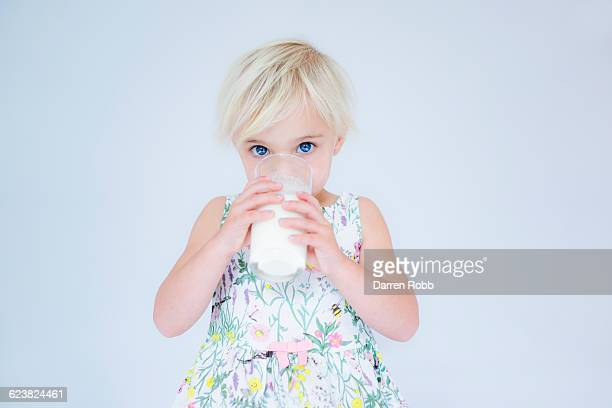 Young girl drinking milk from a glass