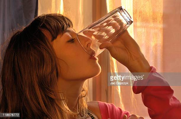 young girl drinking out of an empty glass - depczyk stock pictures, royalty-free photos & images