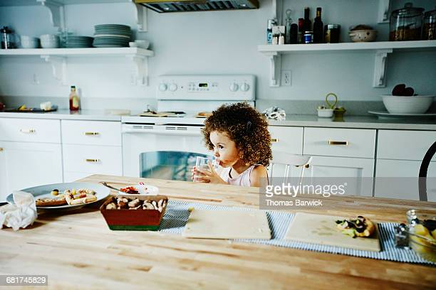 young girl drinking water at kitchen table - dirty little girls photos stock pictures, royalty-free photos & images