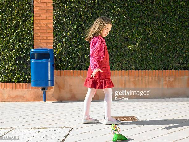 Young girl (5-7) dropping litter on pavement next to public bin, Alicante, Spain,
