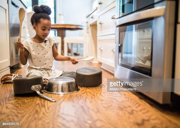 Young girl (6yrs) drumming on pots and pans in kitchen