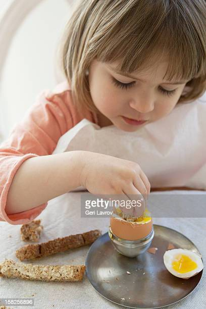 Young girl eating a hard boiled egg
