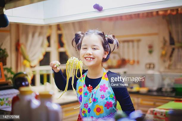 young girl eating and cooking spaghetti - carol cook stock pictures, royalty-free photos & images