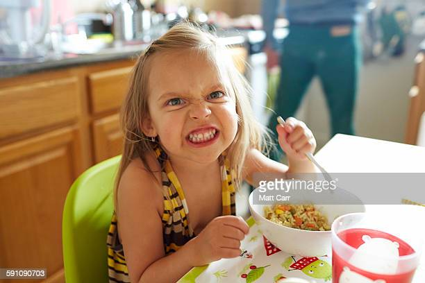 Young girl eating angrily