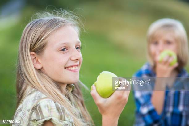 young girl eating apple on a family picnic - kid girl eating apple stock photos and pictures
