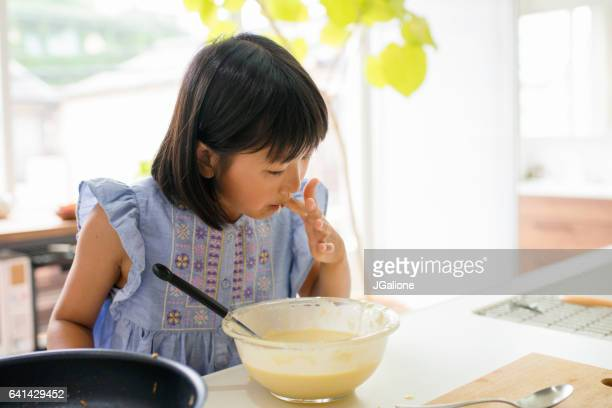 Young girl eating batter