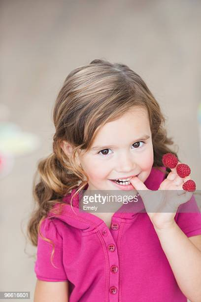 young girl eating berries from fingers