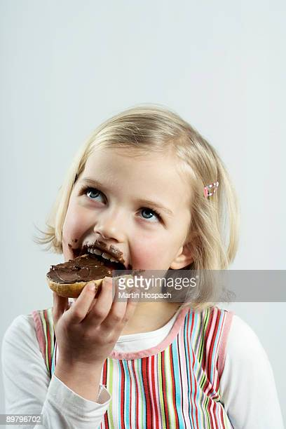 A young girl eating bread and chocolate spread