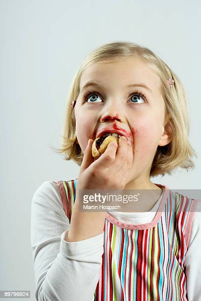 A young girl eating bread and jam